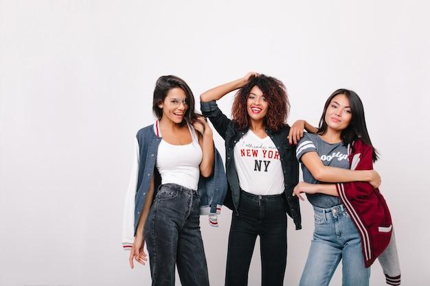 Feliz garota latina em jeans se divertindo com os colegas de universidade posando com um sorriso. retrato interior da adorável senhora africana em pé entre amigos e brincando com o cabelo encaracolado.