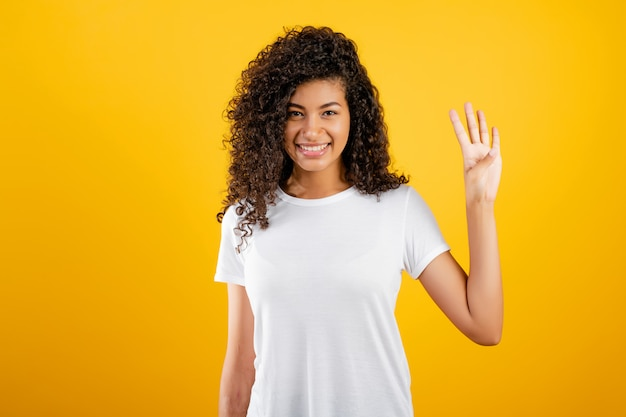 Feliz garota negra mostrando quatro dedos isolados sobre amarelo