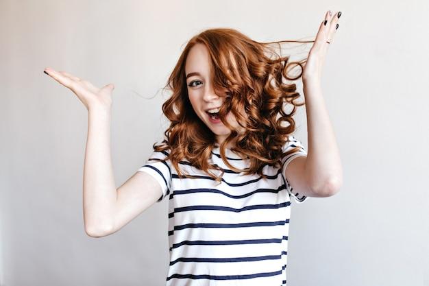 Feliz garota ruiva com pele clara brincando. retrato interno de uma mulher ruiva caucasiana se divertindo durante a sessão de fotos.