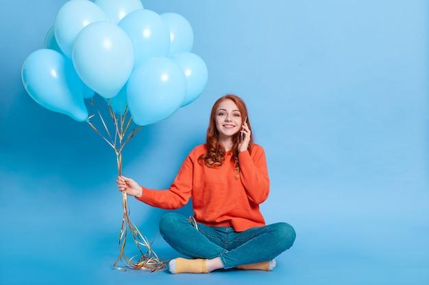 Feliz garota ruiva com suéter casual e jeans posando isolado na parede azul