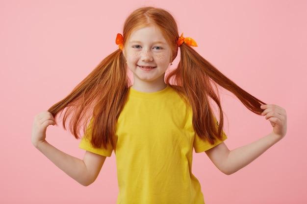 Feliz garota ruiva de sardas pequenas leva suas duas caudas, amplamente sorrindo e parece fofa, usa uma camiseta amarela, fica sobre fundo rosa.