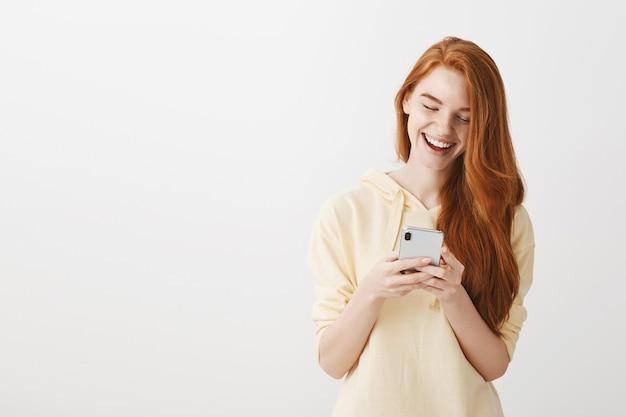 Feliz garota ruiva trocando mensagens de texto olhando para o smartphone com um sorriso