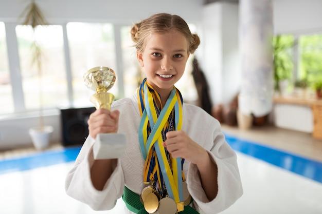 Feliz garota talentosa praticando aikido mostrando seus prêmios