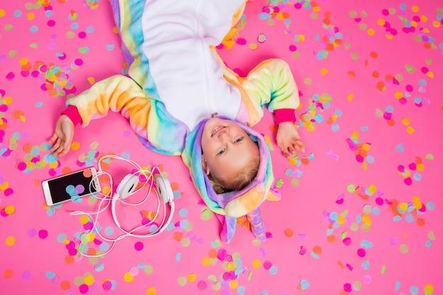 Feliz garotinha loira no unicórnio kigurumi ouve música segurando o smartphone na mão em uma superfície rosa