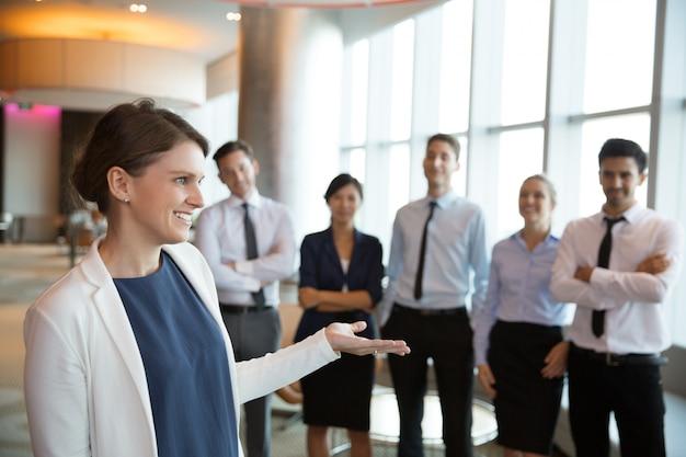 Feliz gerente executivo fêmea com equipe