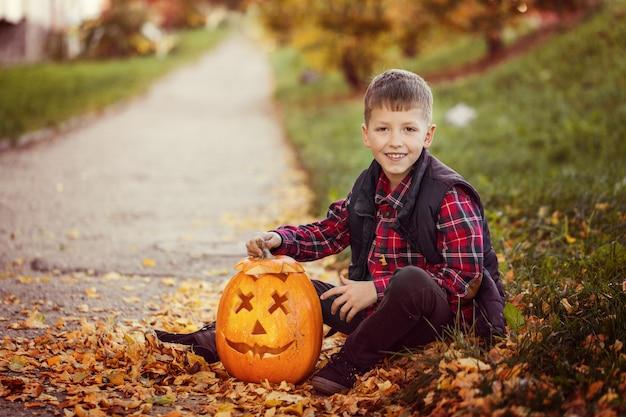 Feliz gracinha menino com abóbora de halloween no outono park.