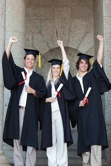 Feliz graduado levantando o braço