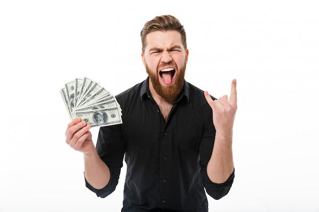 Feliz gritando homem de negócios barbudo na camisa segurando o dinheiro