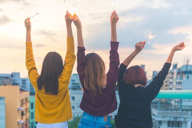 Feliz grupo de amigas asiáticas, desfrute e jogue o sparkler na festa no topo do telhado no por do sol à noite