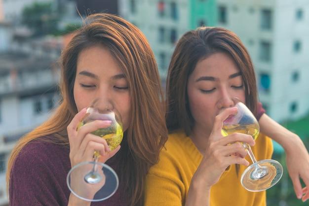 Feliz grupo de amigas asiáticas goza de rir e alegre copo de vinho espumante na festa na cobertura