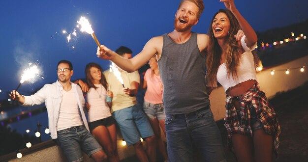 Feliz grupo de amigos acendendo fogos de artifício e curtindo a liberdade