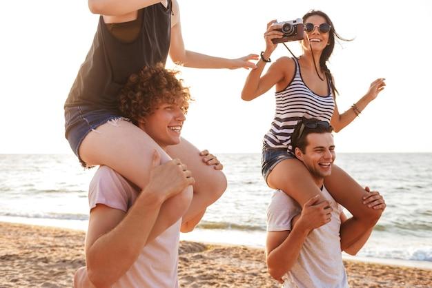 Feliz grupo de amigos amando casais caminhando ao ar livre na praia se divertindo mulher segurando a câmera fotografando.