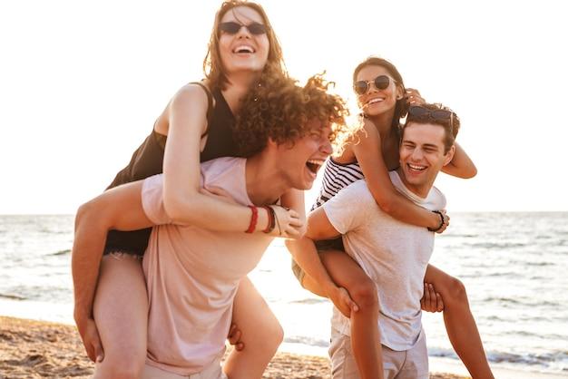 Feliz grupo de amigos amando casais caminhando ao ar livre na praia se divertindo