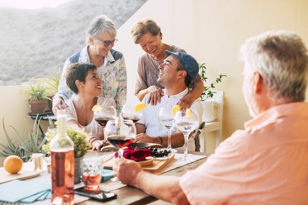 Feliz grupo de amigos ao ar livre comemorando e se divertindo juntos durante um jantar no terraço de casa