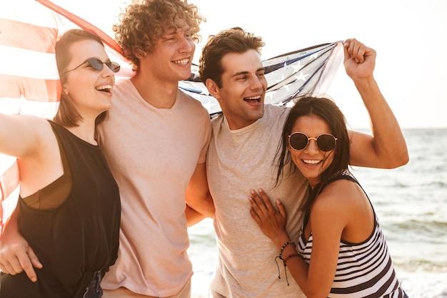 Feliz grupo de amigos ao ar livre na praia segurando a bandeira dos eua e se divertindo