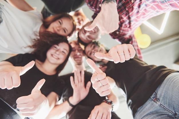 Feliz grupo de amigos com as mãos juntas no meio