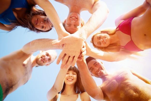 Feliz grupo de amigos dando cinco em círculo sob o sol
