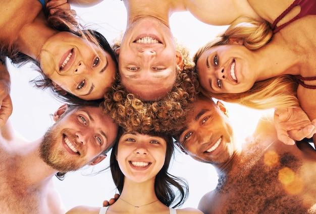 Feliz grupo de amigos em círculo sob o sol no verão