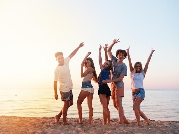 Feliz grupo de amigos erguendo as mãos para o céu