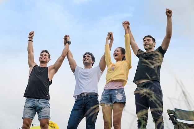 Feliz grupo de amigos mãos levantadas juntos