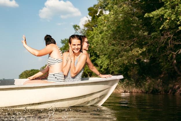 Feliz grupo de amigos se divertindo enquanto riem, espirrando água e nadando no rio