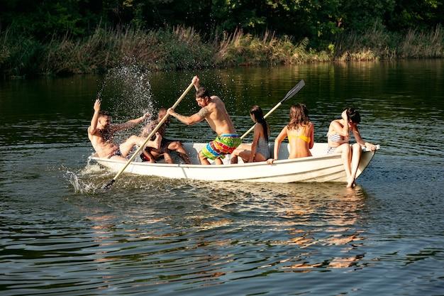 Feliz grupo de amigos se divertindo enquanto rindo e nadando no rio. homens e mulheres alegres em traje de banho em um barco na beira do rio em um dia ensolarado. verão, amizade, resort, conceito de fim de semana.