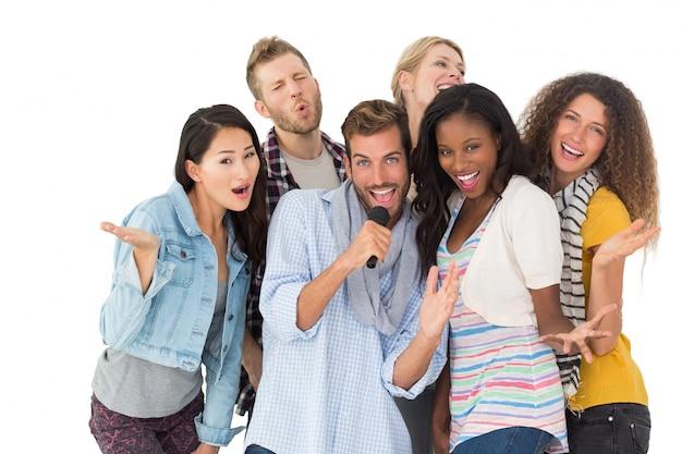 Feliz grupo de amigos se divertindo fazendo karaoke