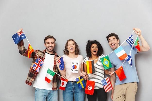 Feliz grupo de amigos segurando muitas bandeiras internacionais.