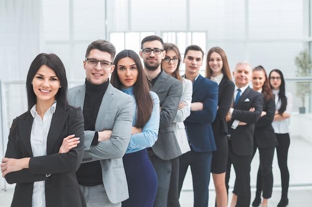 Feliz grupo de diversos jovens em pé em uma fileira. o conceito de trabalho em equipe