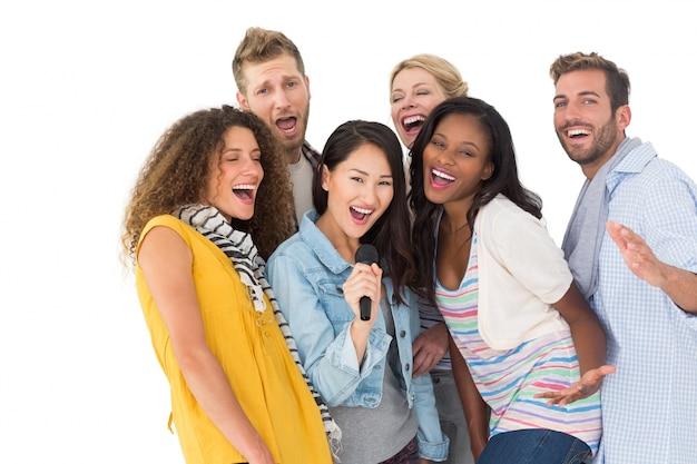 Feliz grupo de jovens amigos se divertindo fazendo karaoke