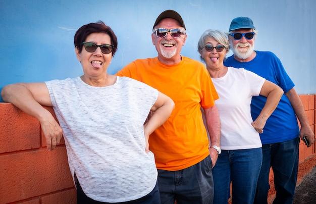 Feliz grupo de quatro pessoas sênior em amizade em pé contra uma parede laranja e azul, sorrindo e gesticulando. caras alegres e engraçadas.