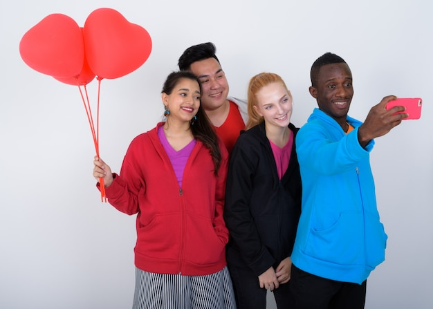 Feliz grupo diversificado de amigos multiétnicos sorrindo e tirando selfie