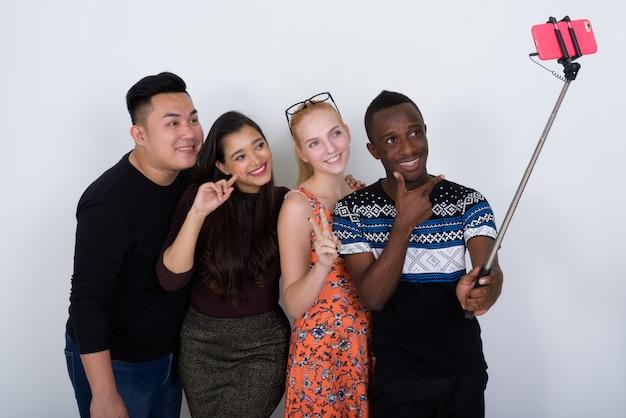 Feliz grupo diversificado de amigos multiétnicos sorrindo enquanto tiravam uma selfie