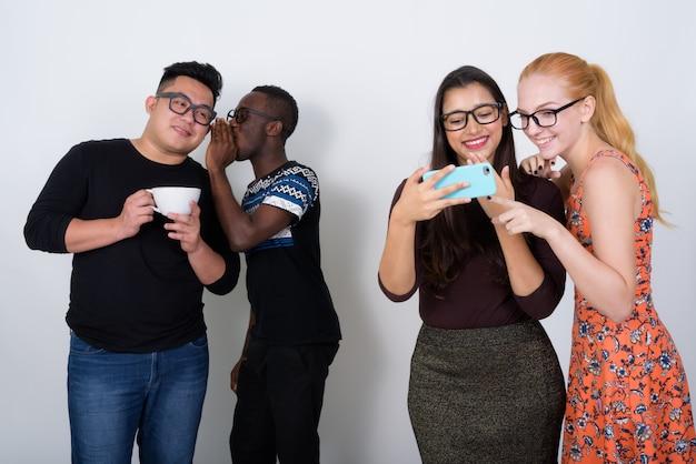 Feliz grupo diversificado de amigos multiétnicos sorrindo enquanto usam telefones