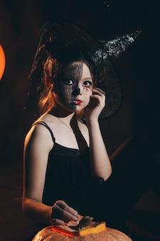 Feliz halloween bruxinha bonitinha com uma grande abóbora. menina linda criança fantasiada de bruxa ao ar livre.