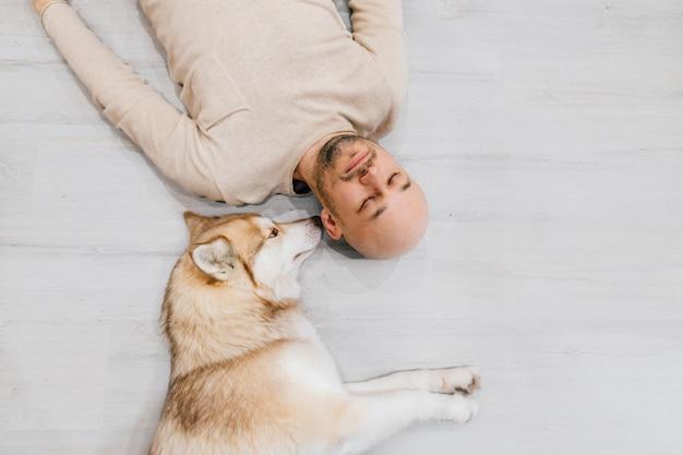 Feliz homem adulto deitado no chão de madeira com seu adorável husky perto dele