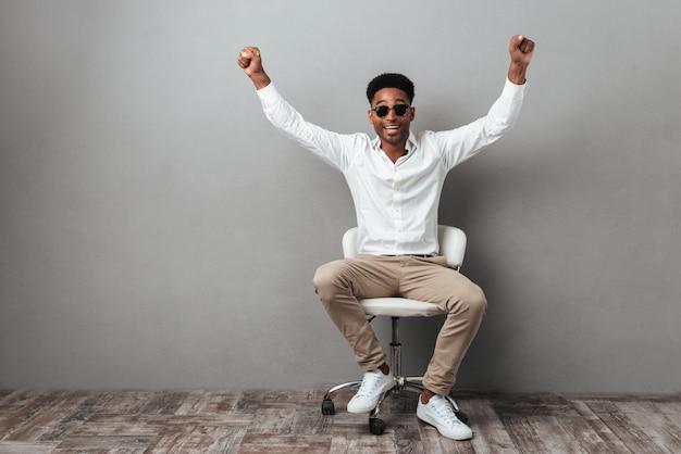 Feliz homem africano animado em óculos de sol comemorando sucesso