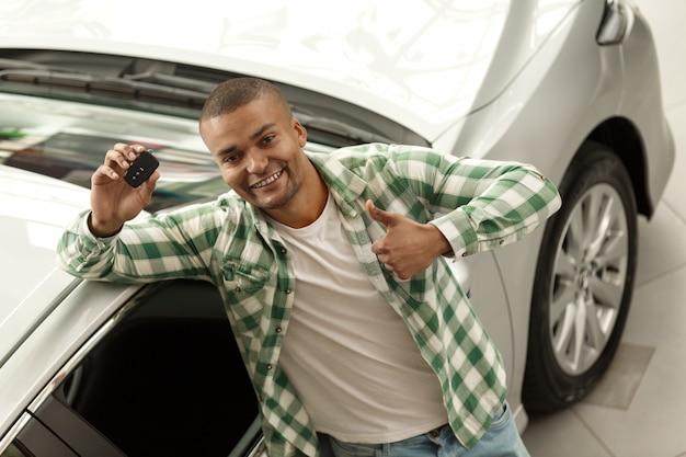 Feliz homem africano bonito mostrando os polegares para cima segurando as chaves do carro na concessionária.