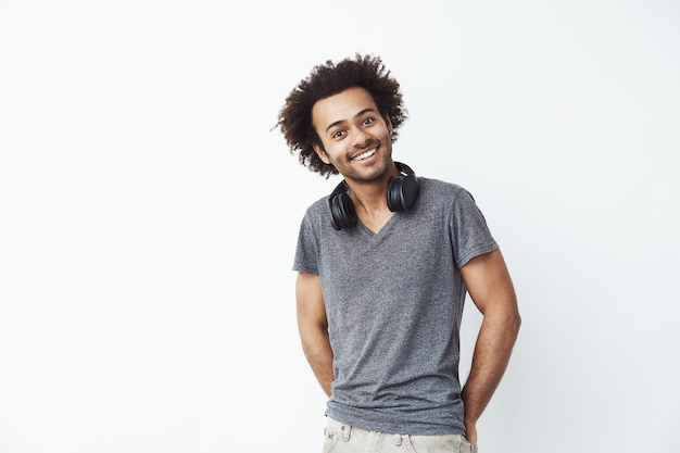 Feliz homem africano com fones de ouvido na sua nech ouvindo streaming de música
