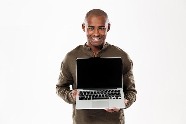 Feliz homem africano mostrando a tela do computador portátil em branco e olhando
