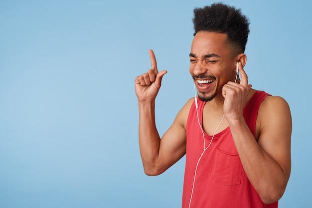 Feliz homem afro-americano atraente em uma camisa vermelha ouve música legal, segura o fone de ouvido com a mão esquerda, fecha os olhos, canta e dança em voz alta, fica de pé.