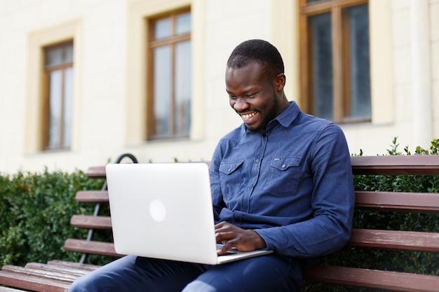 Feliz homem afro-americano trabalha em seu laptop sentado no banco do lado de fora