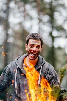 Feliz homem alegre louco segurando lenha ardente nas mãos