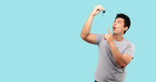 Feliz homem asiático, cara segurando uma chave de carro e apontando para ele, na parede de luz azul