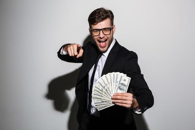 Feliz homem atraente de óculos e terno preto, segurando o monte de dinheiro enquanto aponta com o dedo em você