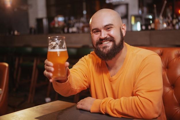 Feliz homem barbudo bonito sorrindo alegremente brindando com seu copo de cerveja no pub