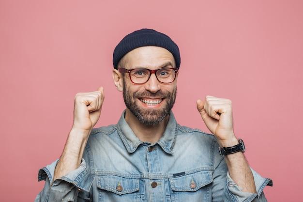 Feliz homem barbudo, com olhos azuis e expressão alegre aperta os punhos, sente-se vencedor