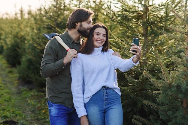 Feliz homem barbudo e sua linda namorada fazendo foto de selfie na plantação de árvores de natal.