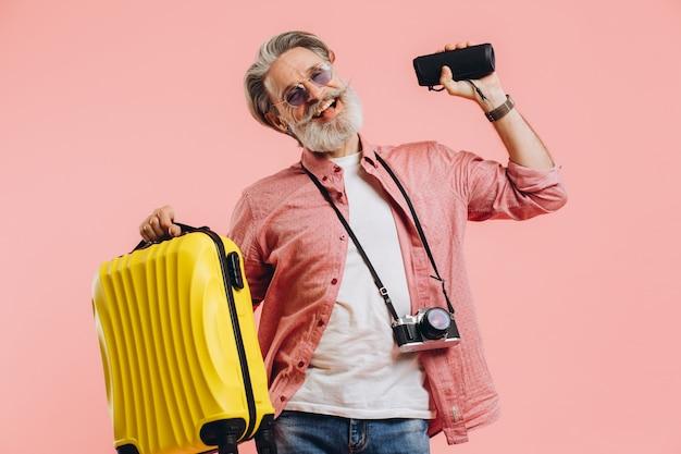 Feliz homem barbudo elegante em óculos de sol com câmera segurando uma mala e um alto-falante portátil