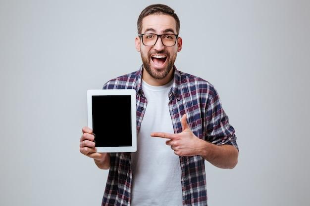 Feliz homem barbudo em óculos mostrando a tela do computador tablet em branco